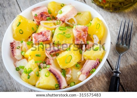 Italian food: salad with octopus, potatoes and onions on rustic background - stock photo