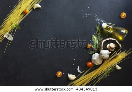 Italian food, spaghetti recipe ingredient with vintage fork on black texture background. Overhead view. - stock photo