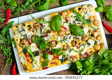 Italian Frittata with slices of fresh greens, food - stock photo