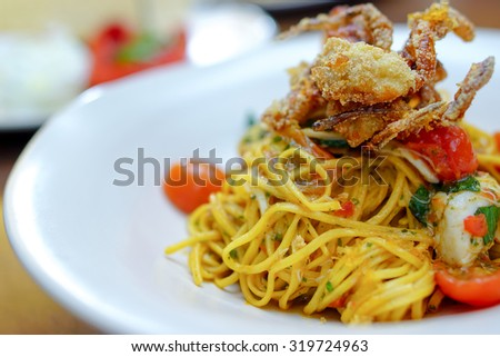 Italian fusion food - pan fried spaghetti with olive oil with crab and topping with deep fried soft shell crab - stock photo