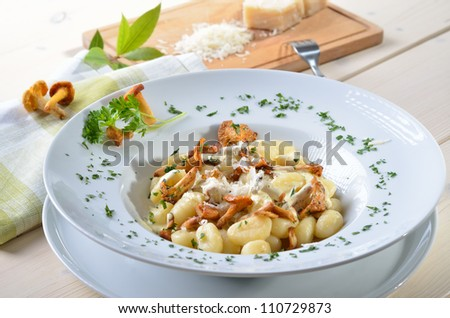 Italian gnocchi with fresh fried chanterelles, sauce and parmesan cheese - stock photo
