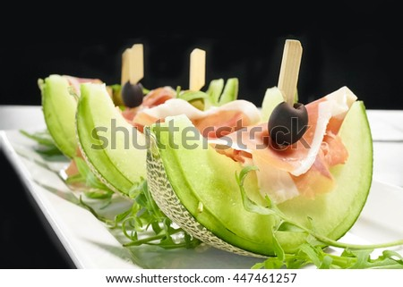 Italian Gourmet Appetiser : Fresh Melon with Prosciutto (Parma Ham). Selective focus on the edge of the first melon (highlight's area) isolated on black background - stock photo