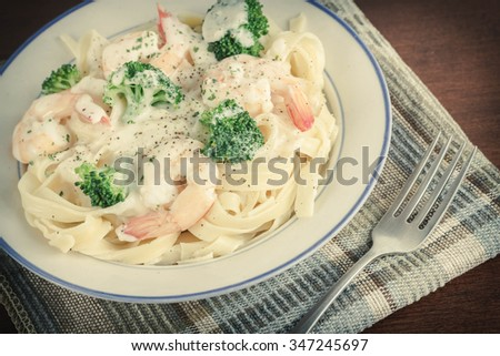 Italian health conscious fettuccine alfredo shrimp with broccoli florets - stock photo