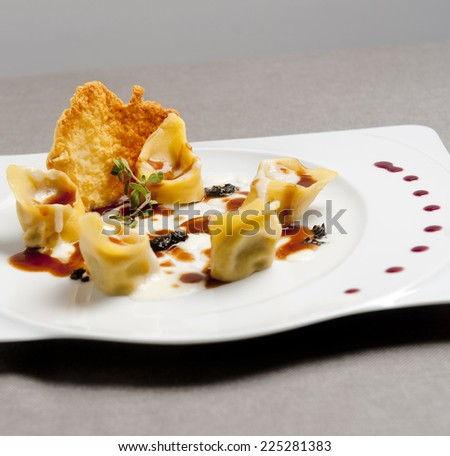 Italian homemade ravioli with cheese in a white plate - stock photo