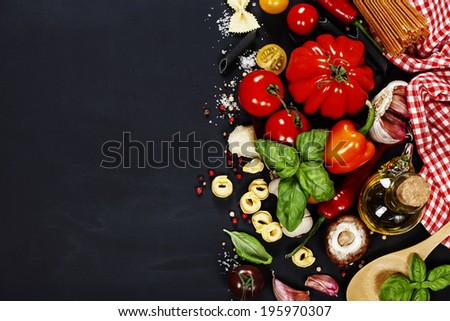 Italian ingredients - pasta, vegetables, spices, cheese - on dark background - stock photo