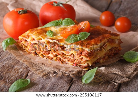 Italian lasagna with basil close-up on paper. horizontal rustic style - stock photo