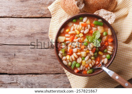 Italian minestrone soup and bread on the table. horizontal view from above  - stock photo