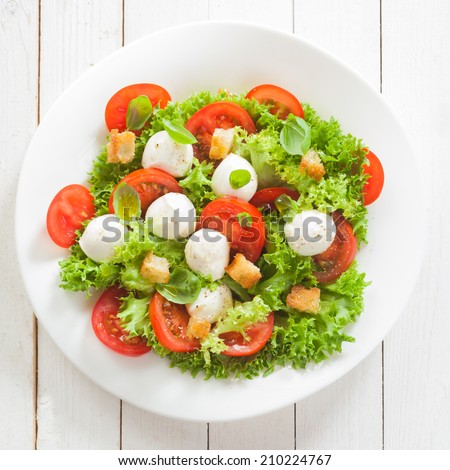 Italian mozzarella cheese and tomato salad with tomatoes and crisp crunchy fried bread cretins, view from above on a plate on white wooden boards, square format - stock photo