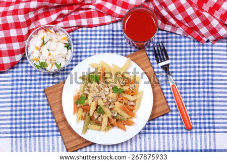 Italian multi-colored pasta. A pasta dish. Cabbage salad, tablecloth, kitchen board and a plate of pasta on the table. A delicious lunch. - stock photo