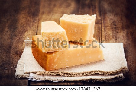 Italian  Parmesan Cheese on Wooden Background close up. Piece of Parmigiano  cheese on a napkin, rustic style. - stock photo