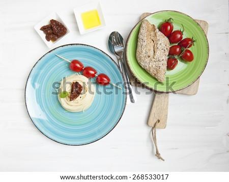 Italian pasta dish - fresh and dried tomatoes, bread, olive oil, - stock photo