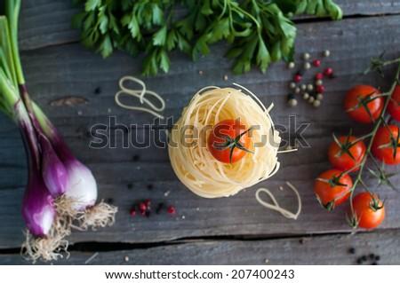 Italian pasta fettuccine nest, cherry tomato, parsley, onion on wooden table - stock photo