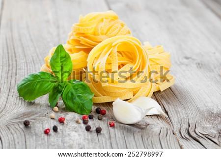 Italian pasta fettuccine nest, on wooden background - stock photo