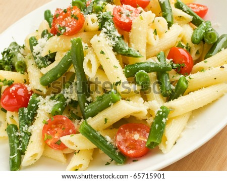 Italian pasta penne with cherry tomatoes and green beans. Shallow dof ...