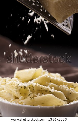 Italian pasta penne with grated parmesan cheese - stock photo