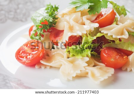 Italian pasta salad with lettuce and cherry tomato - stock photo