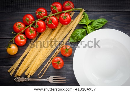 Italian pasta spaghetti mafaldine regionali, served plate with fork, on a wooden table with bunch tomatoes.  - stock photo