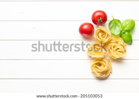 italian pasta tagliatelle, tomatoes and basil leaves on white table - stock photo