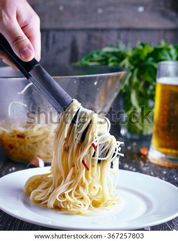 Italian pasta with garlic and chili. Hand with tongs or fork move spaghetti pasta with garlic, oil and chili to a white plate on wood background - stock photo