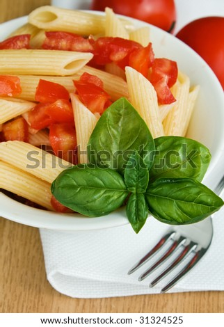 Italian pasta with tomato and basil on the table - stock photo