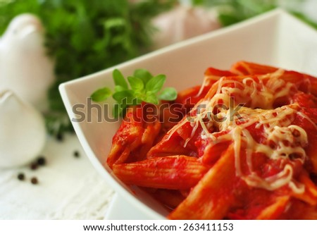 Italian pasta with tomato sauce and parmesan cheese on a top. Served in a white bowl. Typical delicious Italian food, meal, dish. Close-up, nobody. Restaurant. - stock photo