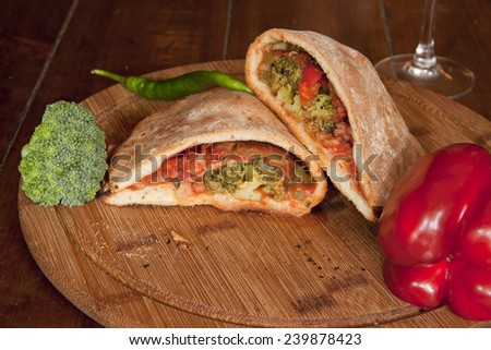 italian pizza calzone on a wooden plate - stock photo