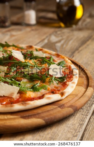 "Italian pizza ""Parma""  lies on beautiful wooden table. On top of the pizza thinly sliced ham, arugula and parmesan cheese slices. Nearby are the containers with spices and olive oil. - stock photo"