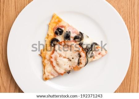 Italian Pizza Slice Served On White Plate - stock photo