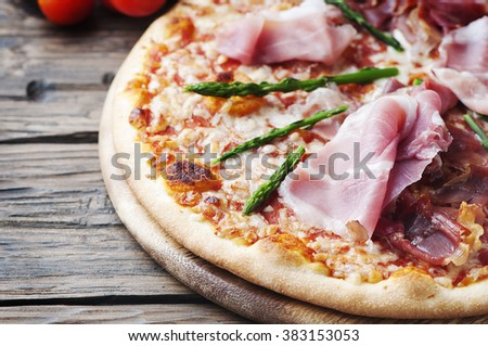 Italian pizza with ham and asparagus, selective focus - stock photo