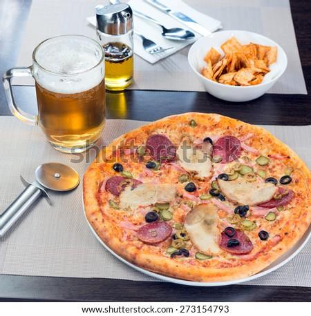 Italian pizza with ham tomato and olives - stock photo