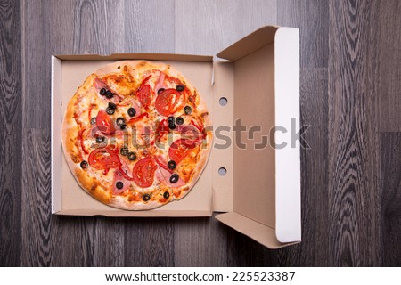 Italian pizza with ham, tomatoes, and olives in box, on gray table background  - stock photo