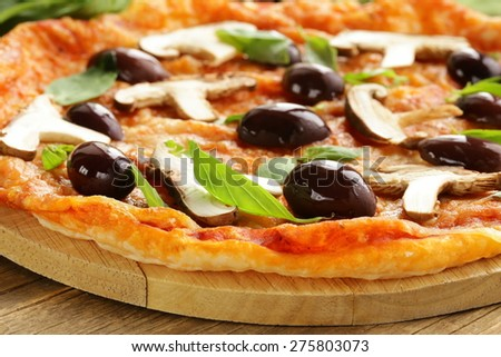 Italian pizza with olives and mushrooms on a wooden board - stock photo