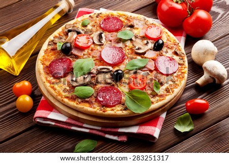 Italian pizza with pepperoni, tomatoes, olives and basil on wooden table - stock photo