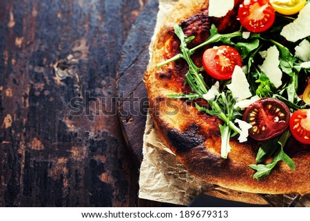 Italian pizza with rucola and cherry-tomatoes - stock photo