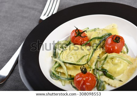 Italian ravioli filled with courgette and ricotta, served with oven baked cherry tomatoes and a cream sauce - stock photo