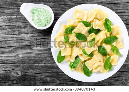 Italian Ravioli filling with  ricotta cheese and spinach decorated with  leaves on a white dish, creamy green sauce in a gravy boat on a cutting board, top view - stock photo