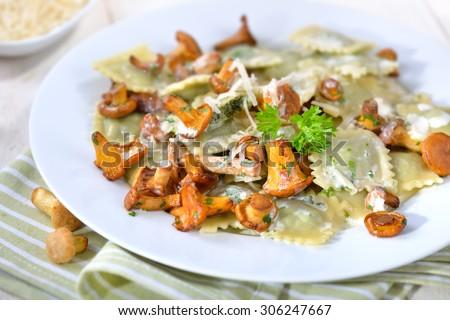Italian ravioli with fresh roasted chanterelles and creamy parmesan cheese sauce  - stock photo