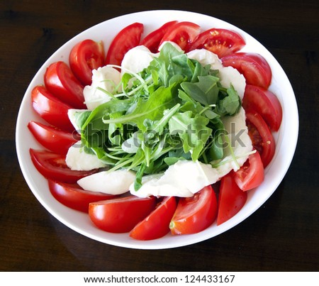 Italian salad with absolute fresh summer ingredients: mozzarella, ripe red tomatoes and rucola - stock photo