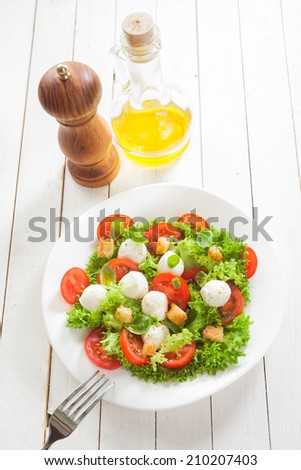 Italian salad with mozzarella cheese pearls,, tomato, lettuce, herbs and croutons served with virgin olive oil and pepper - stock photo