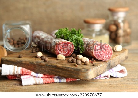 Italian salami on wooden cutting board, on wooden background - stock photo