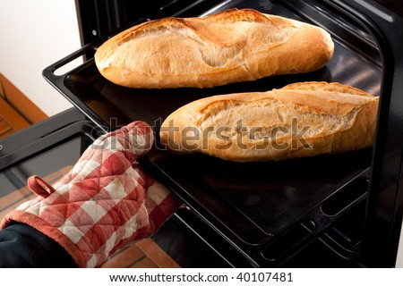 Italian Sfilatino bread served on a bed of red and green leaves and cut in slices - stock photo