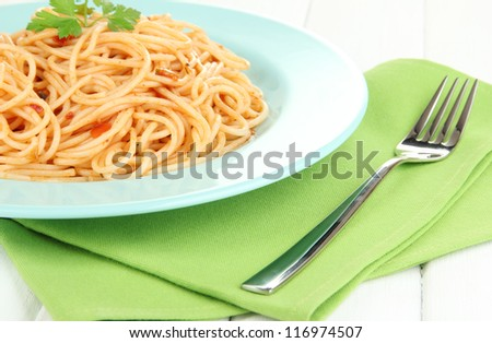 Italian spaghetti in plate on wooden table close-up - stock photo