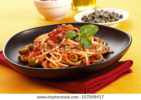 Italian spaghetti with tomato sauce, olives and capers - stock photo