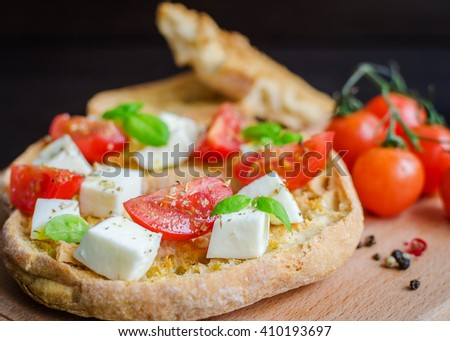Italian starter friselle. Classical frisella tomato, cheese mozzarella and basil with oregano and olive oil. Dried bread called freselle on wooden board. Italian food. Healthy vegetarian food. - stock photo