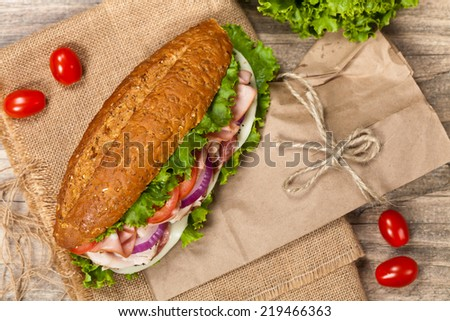Italian Sub Sandwich with Salami, Tomato, and Lettuce. Selective focus.  - stock photo