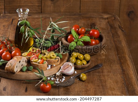 Italian tomato bruschetta with chopped olives, garlic, herbs and olive oil on  ciabatta bread on the wooden table - stock photo