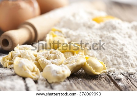 Italian tortellini on wooden vintage wooden board  - stock photo