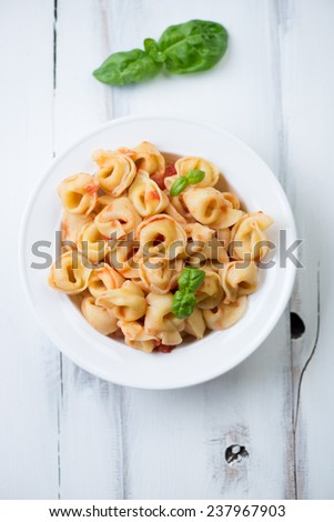 Italian tortellini with tomato sauce over white wooden surface - stock photo