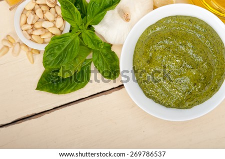Italian traditional basil pesto sauce ingredients on a rustic table - stock photo