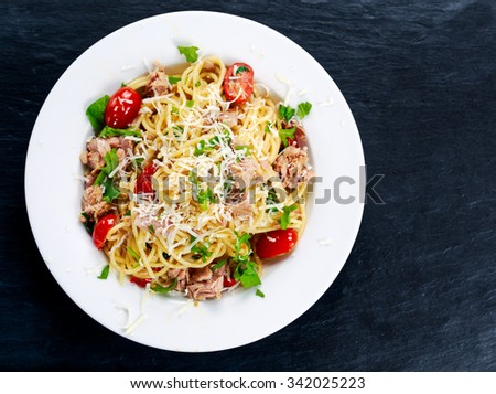 Italian Tuna Pasta spaghetti with tomato, chili, Parmesan cheese and wild rocket  lives. on old blue stone table - stock photo
